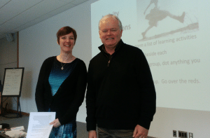 Beth Cougler Blom and David Stevenson standing in front of a screen and smiling at the camera