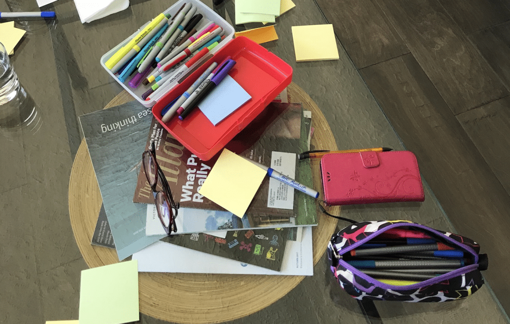 Pens and sticky notes and magazines strewn on a glass table.